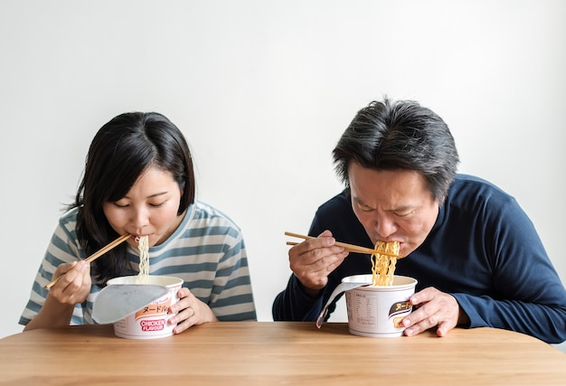 Couple asiatique manger des nouilles instantanées
