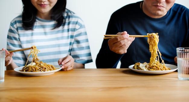 Couple asiatique manger des nouilles