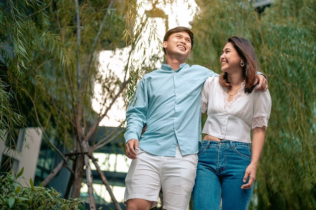 Couple asiatique marchant dans le parc de l'hôteldans la main d'un homme tenant un livre et dans une femme tenant