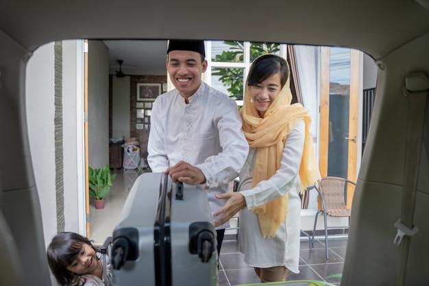 Couple asiatique musulman a mis la valise dans le coffre de la voiture