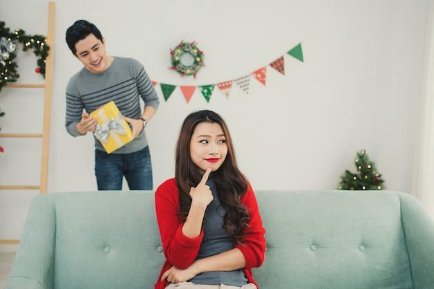 Couple asiatique de noël. un bel homme donnant à sa petite amie/femme un cadeau à la maison pour célébrer le nouvel an