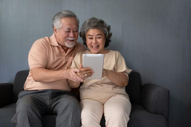 Couple asiatique de personnes âgées souriant et regardant la même tablette sur le canapé à la maison