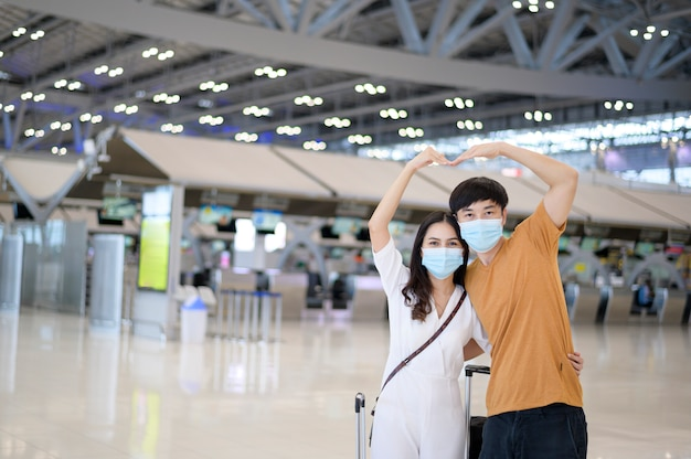 Un couple asiatique porte un masque de protection à l'aéroport international, voyage sous la pandémie de covid-19,