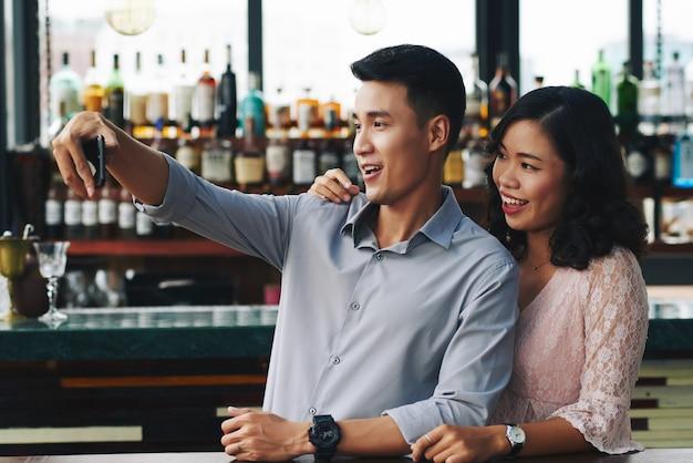 Couple asiatique prenant selfie sur smartphone au bar