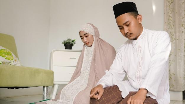 Couple asiatique priant ensemble à la maison