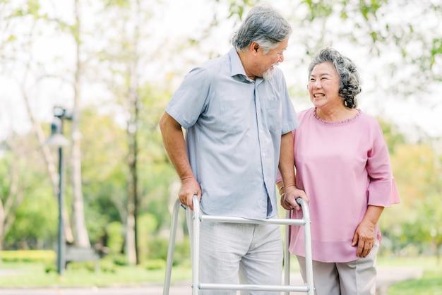 Couple asiatique rire en se promenant avec promeneur dans le parc