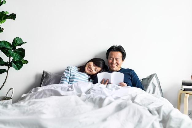 Couple asiatique se détendre sur le lit ensemble