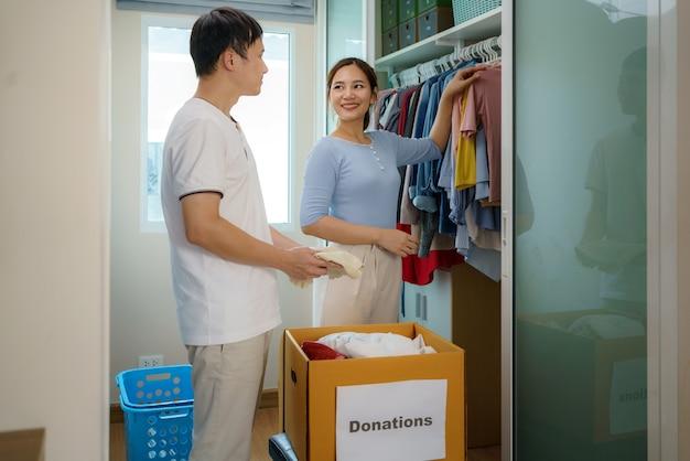 Un couple asiatique se tient près d'un placard de vêtements dans le vestiaire et discute des vêtements à donner pour les emporter dans la boîte de dons.