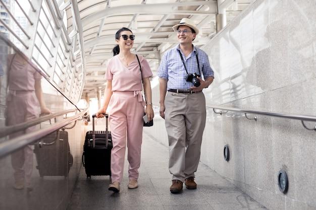 Couple asiatique senior avec une femme faisant glisser une valise et parler joyeusement avec sourire à l'aéroport pour se préparer à voyager. le bonheur des tantes et des oncles en voyageant voyage ensemble avec le sourire.
