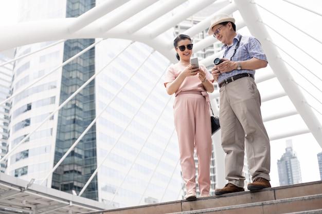Couple asiatique senior jouant mobile à l'extérieur.