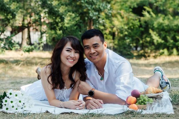 Un couple asiatique souriant en train de pique-niquer dans un parc, allongé sur le ventre. homme et femme en vêtements blancs à l'ombre d'un arbre.