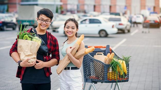Couple asiatique sympathique tenir des sacs écologiques en papier avec des aliments sains biologiques dans les mains tout en se tenant près du centre commercial du magasin. shopping en famille heureuse le week-end.