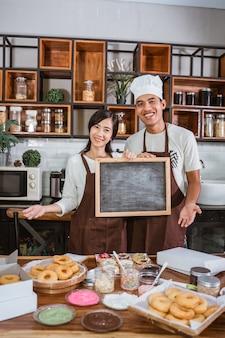 Couple asiatique tenant un tableau noir en se tenant debout dans la cuisine
