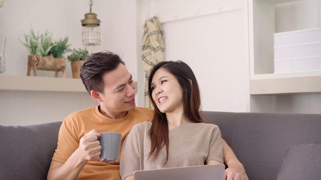 Couple asiatique, utilisation, ordinateur portable, et, boire, chaud, tasse café, dans, salon, à, maison