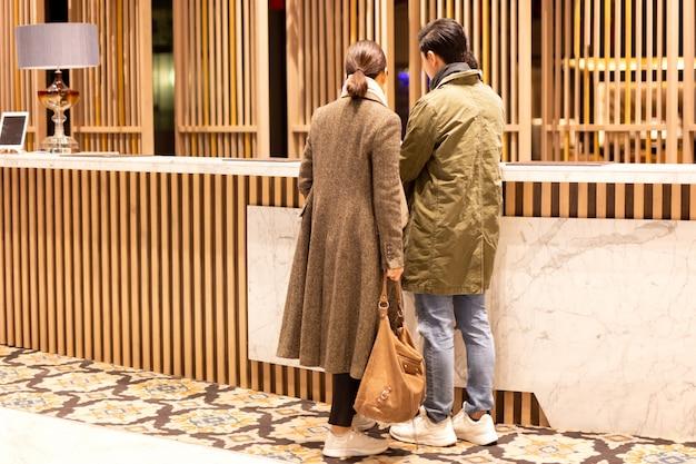Couple asiatique vérifiant à l'hôtel à la réception de l'hôtel.