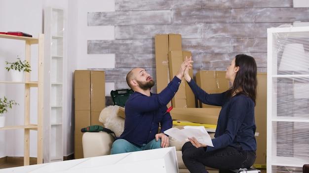 Couple assemblant des meubles dans leur nouvel appartement. le couple fait un high five après le travail.