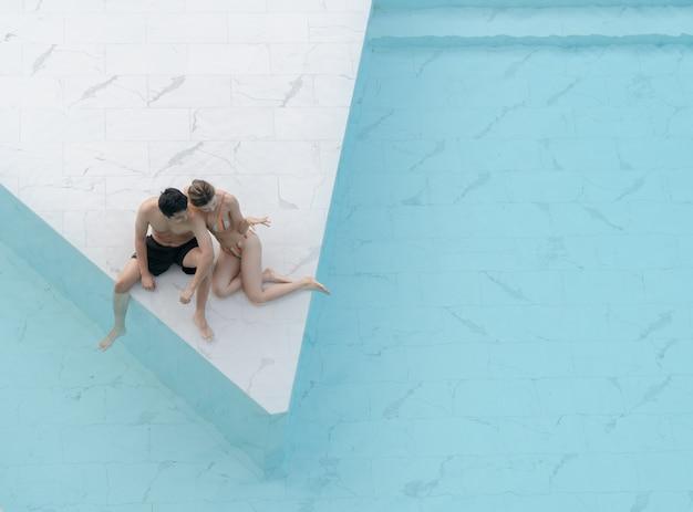 Couple assis au bord de la piscine en carrelage en pierre de marbre blanc avec de l'eau déchirée bleue.