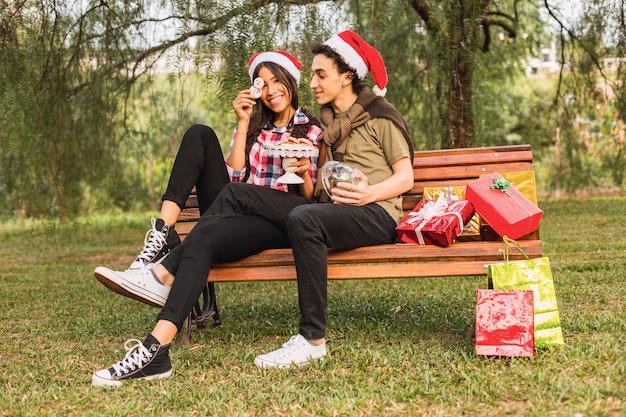 Couple assis sur un banc de parc avec des cadeaux autochtones