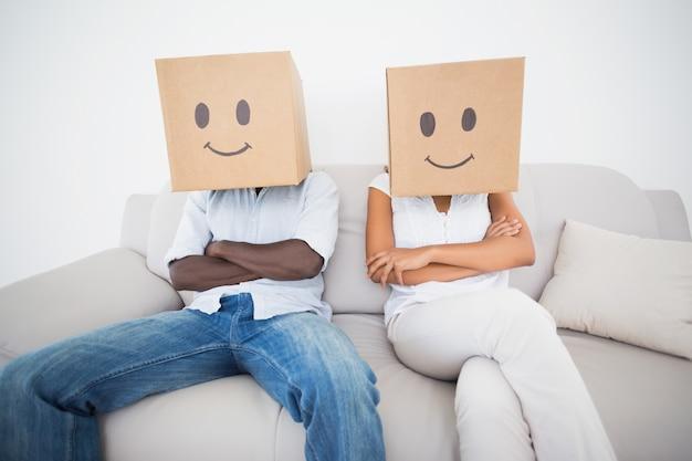 Couple assis sur le canapé avec des boîtes sur la tête