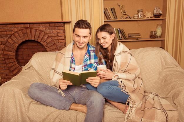 Couple assis sur un canapé avec livre