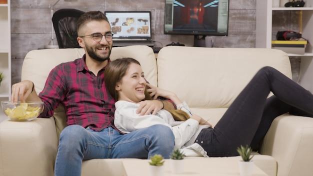 Couple assis sur le canapé et riant en regardant la télévision.