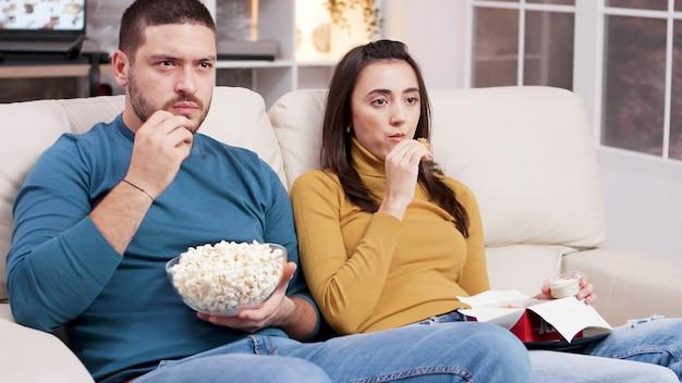 Couple assis sur un canapé en train de manger du poulet frit et du pop-corn en regardant la télévision. couple effrayé après un moment effrayant dans le film.