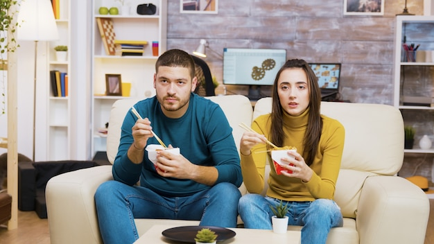 Couple assis sur un canapé en train de manger des nouilles avec des baguettes et de regarder la télévision.