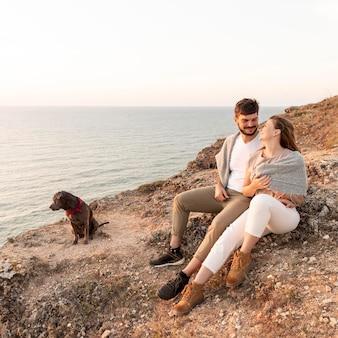 Couple assis à côté de leur chien sur une côte