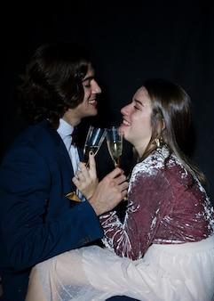 Couple assis avec des coupes à champagne dans les mains