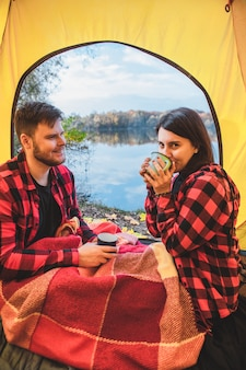 Couple assis dans la tente buvant du thé chaud en regardant le lac d'automne. concept de camping