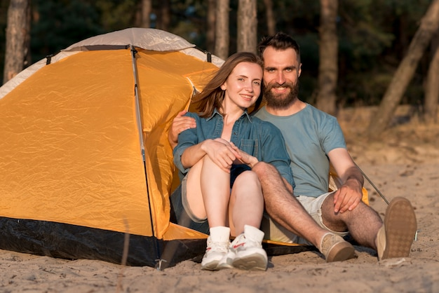 Couple assis dans la tente en regardant la caméra