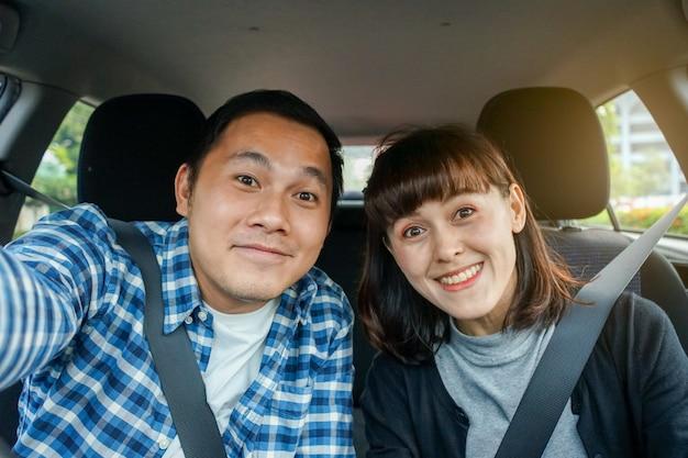 Couple assis dans une voiture et prendre un selfie
