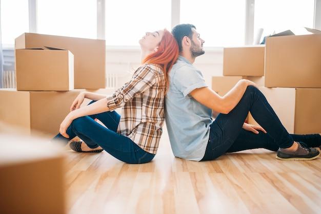 Couple assis dos à l'autre, nouvelle maison