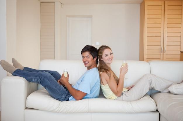 Couple assis dos à dos tout en buvant du vin mousseux