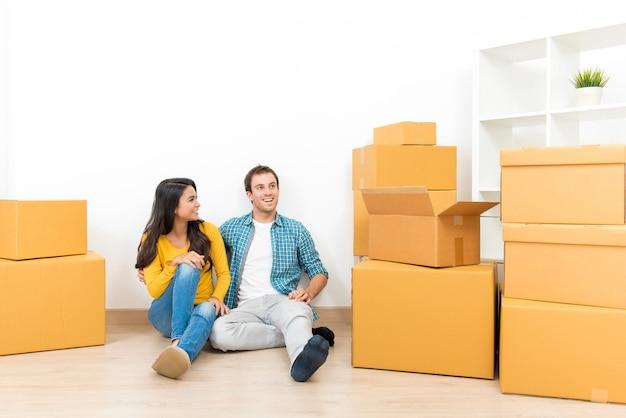 Couple assis ensemble sur le sol après avoir emménagé dans leur nouvelle maison