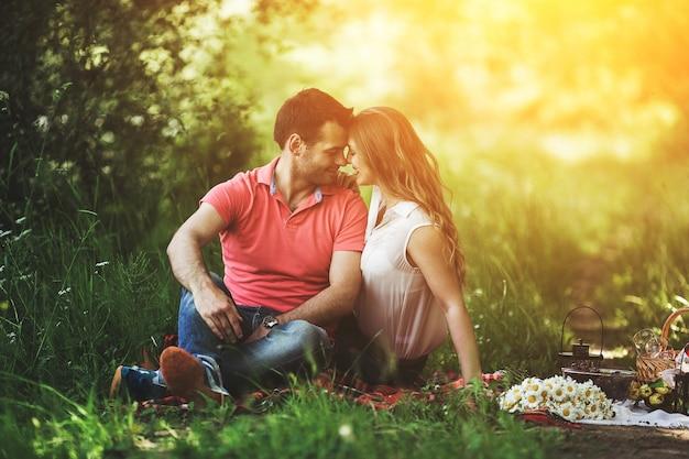 Couple assis sur l'herbe en regardant les yeux de chacun