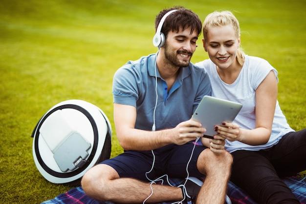 Couple assis sur l'herbe et s'amusant avec une tablette