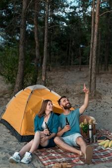 Couple assis, levant les yeux au ciel