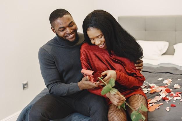 Couple assis sur un lit le jour de la saint-valentin