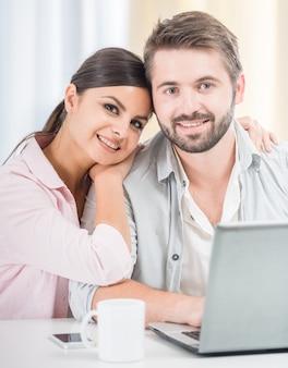 Couple assis à la maison et utilisant un ordinateur portable ensemble.