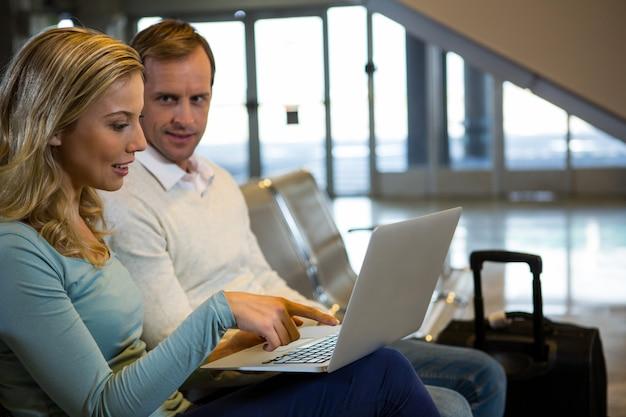 Couple assis avec un ordinateur portable dans la zone d'attente