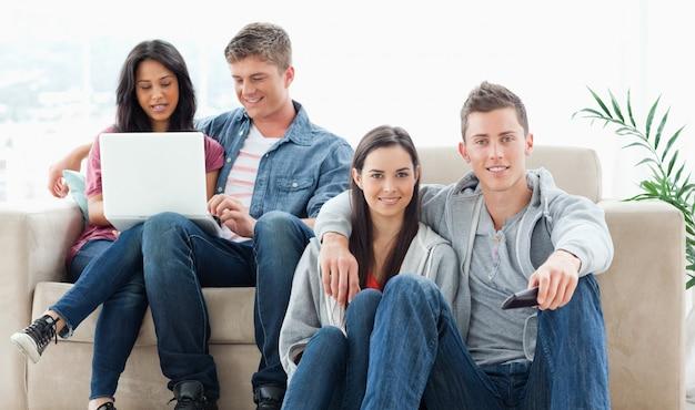 Un couple assis par terre avec une télécommande pendant qu'un autre couple est assis sur le canapé