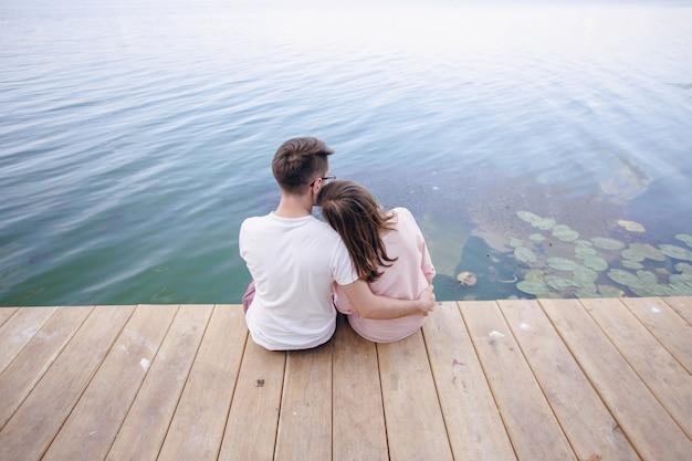 Couple assis sur un quai en bois et sa tête posée sur l'épaule de lui
