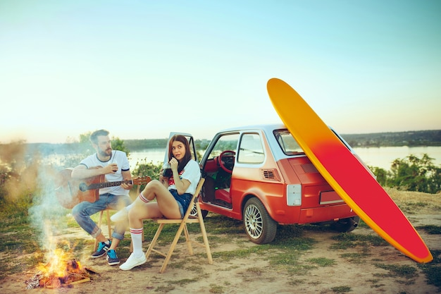 Couple assis et reposant sur la plage à jouer de la guitare un jour d'été près de la rivière
