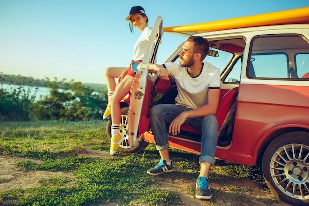 Couple assis et reposant sur la plage un jour d'été près de la rivière