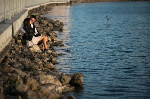 Couple assis sur les rochers en bord de mer