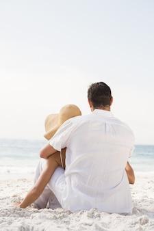 Couple assis sur le sable à la plage