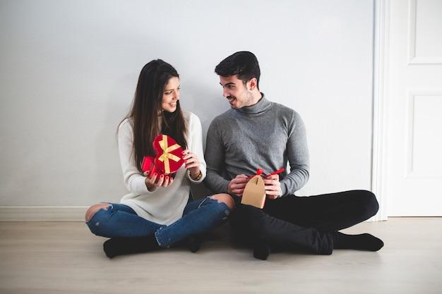 Couple assis sur le sol et elle avec un cadeau rouge