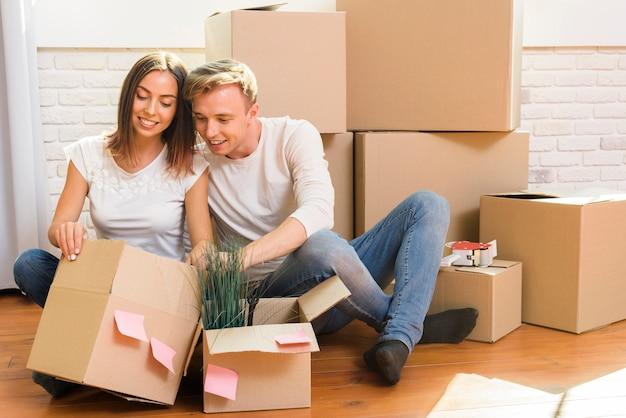 Couple assis sur le sol inspecte une boîte