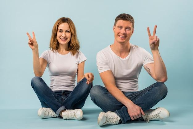 Couple assis sur le sol, montrant le signe de la paix sur fond bleu